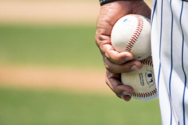 2つの野球ボールを持つ男の人