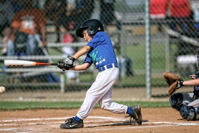 少年野球の選手が右打席でスイングするところ