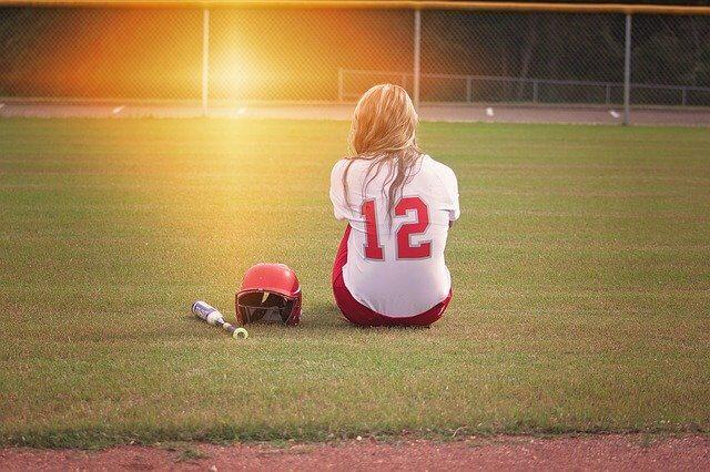 グラウンドに座る女子野球の選手
